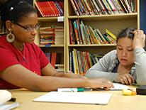 A tutor or teacher reading an assigment on a page to a young student