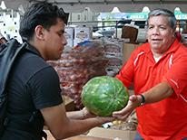 A man at an outdoor food stall handing a watermelon to another man